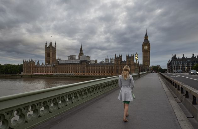 A woman walks on Westminster Bridge towards the Houses of Parliament (file