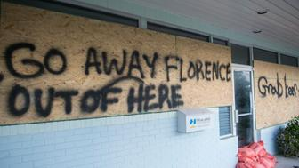 A sign is seen on a boarded up vacation rentals office near Wrightsville beach, North Carolina on September 12, 2018. - People fleeing North and South Carolina clogged coastal highways early Wednesday as Hurricane Florence, a monster Category 4 storm, bore down on the US east coast for a direct hit in a low-lying region dense with beachfront vacation homes.President Donald Trump, warning residents to get out of the way, said the federal government was 'ready for the big one that is coming.' (Photo by ANDREW CABALLERO-REYNOLDS / AFP)        (Photo credit should read ANDREW CABALLERO-REYNOLDS/AFP/Getty Images)