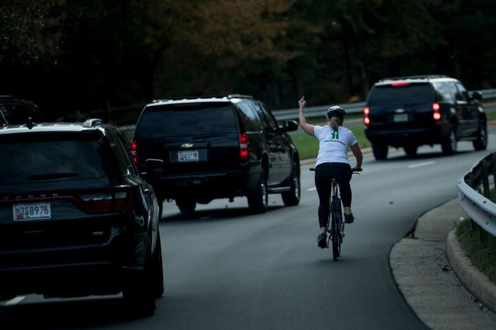 Juli Briskman gestures with her middle finger as President Donald Trump's motorcade passes her in October 2017.
