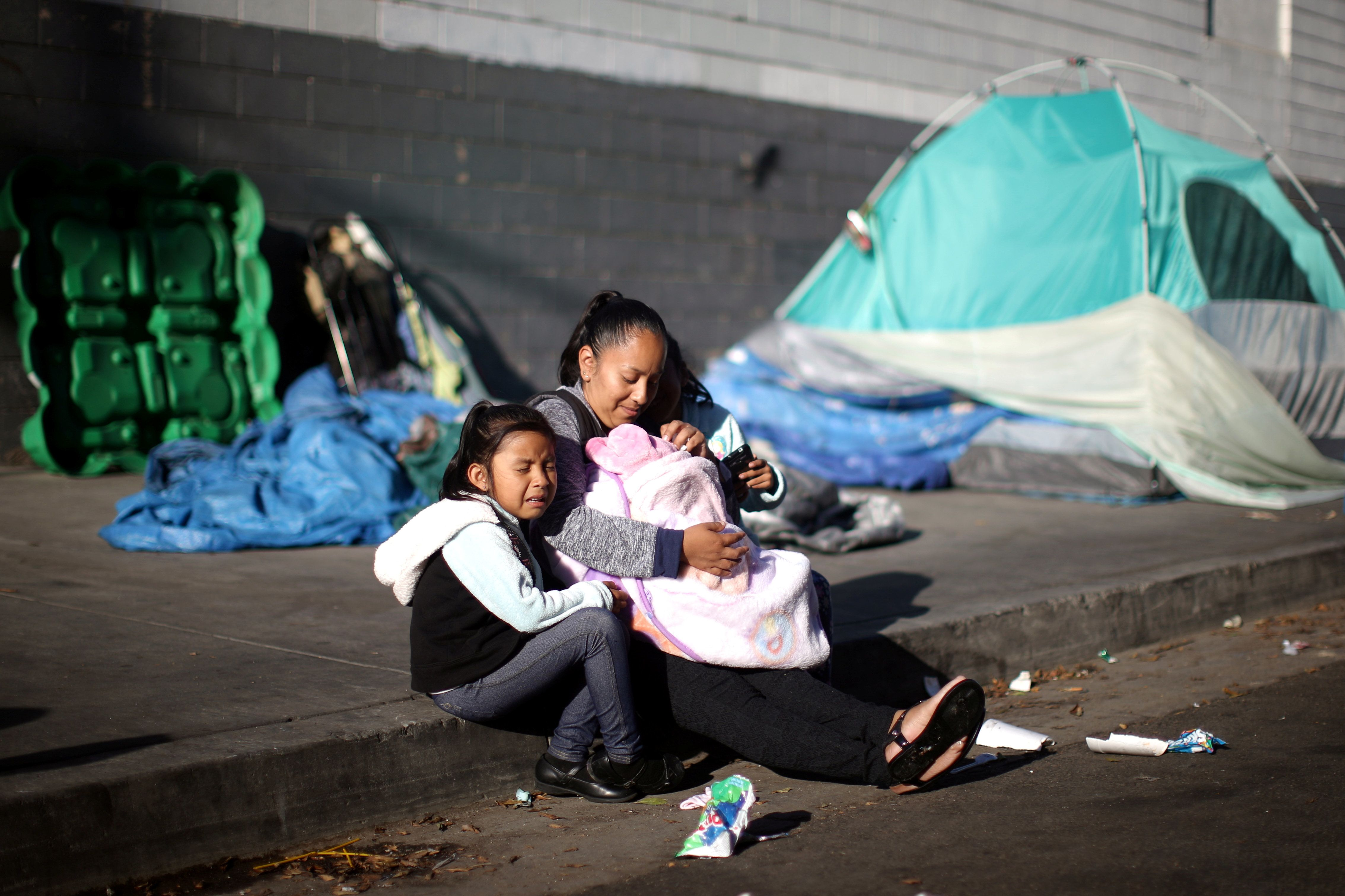 Samantha Cadena sits with her daughters as they wait in line with other needy families to receive free...