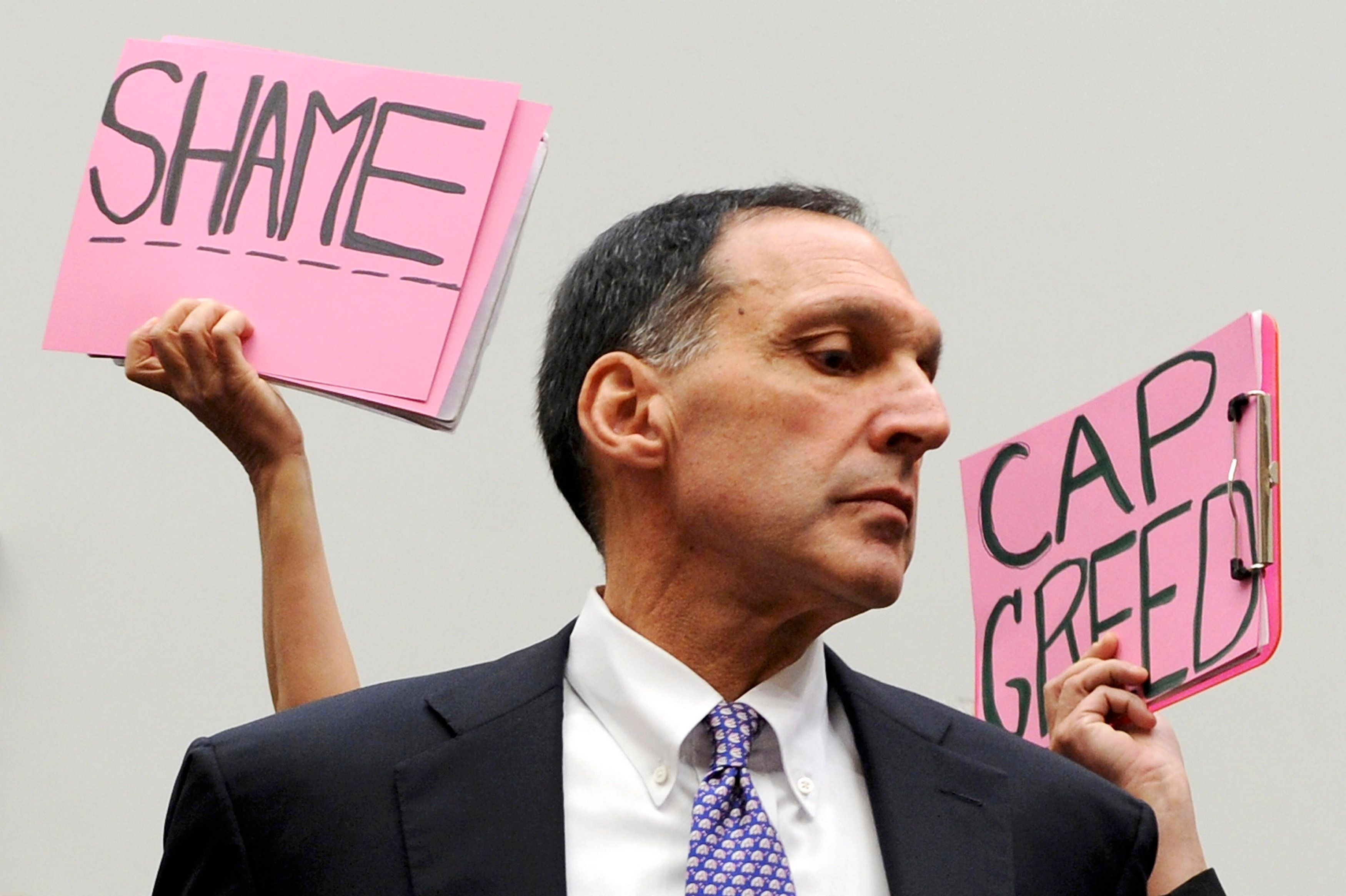 Protesters hold signs behind Dick Fuld at an October 2008 congressional hearing on the causes and effects of the Lehman