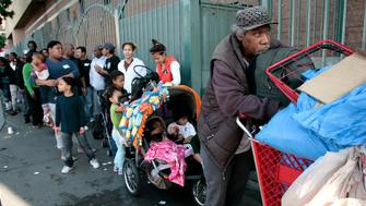 People wait in a line stretching around the block as the homeless and needy are served a free Thanksgiving meal at the Los Angeles Mission on Skid Row in Los Angeles, California November 21, 2012.  REUTERS/Jason Redmond   (UNITED STATES - Tags: SOCIETY POVERTY)