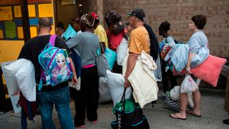 People line up to enter a hurricane shelter at Trask Middle School in wilmington, North Carolina, on September 11, 2018. - Hurricane Florence would deliver a 'direct hit' to the US East Coast, emergency officials warned on September 11, 2018. More than one million people in North Carolina, South Carolina and Virginia have been told to flee their homes as the hurricane churns across the Atlantic Ocean towards the coast. (Photo by Andrew CABALLERO-REYNOLDS / AFP)        (Photo credit should read ANDREW CABALLERO-REYNOLDS/AFP/Getty Images)