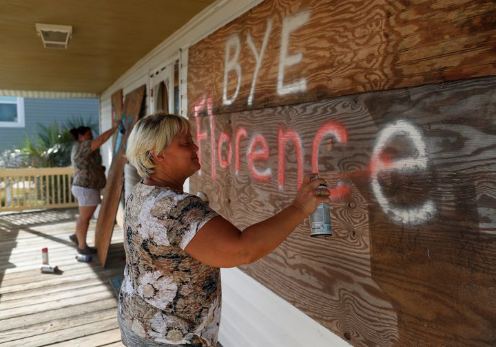 Lisa Evers (Foreground) and her daughter Amanda Hamilton, both of Oak Island, decorate their storm shutters before evacuating