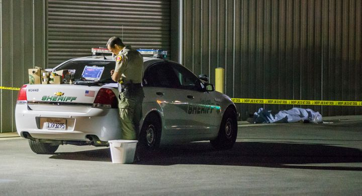 A Kern County sheriff's deputy collects evidence after a series of shootings onWednesday in Bakersfield, Calif.