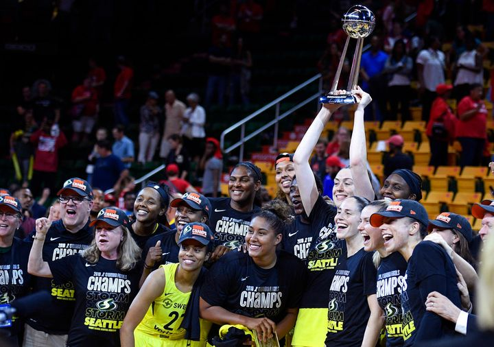 Seattle Storm forward Breanna Stewart holds and poses with the trophy with her teammates after Game 3 of the WNBA basketball