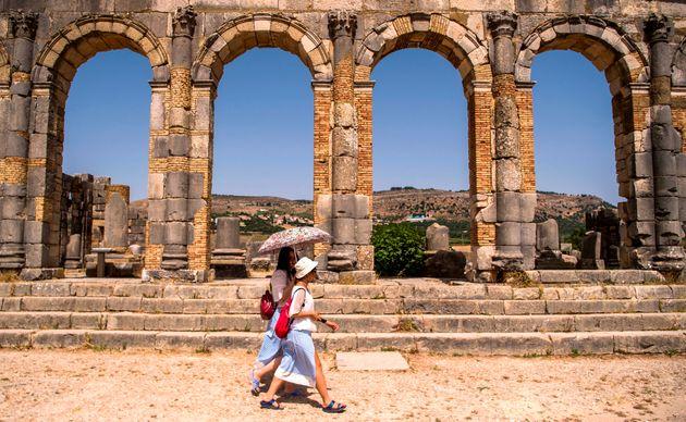 Des touristes marchent dans les anciennes ruines romaines de Volubilis, près de la ville de Moulay...