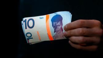 "A man holds a 10 Brixton Pounds note, which is adorned with an image of Brixton native David Bowie in Brixton, south London, January 11, 2016. David Bowie, a music legend who used daringly androgynous displays of sexuality and glittering costumes to frame legendary rock hits ""Ziggy Stardust"" and ""Space Oddity"", has died of cancer. The Brixton Pound is an alternative currency which can be used in businesses in the south London neighbourhood. REUTERS/Stefan Wermuth"