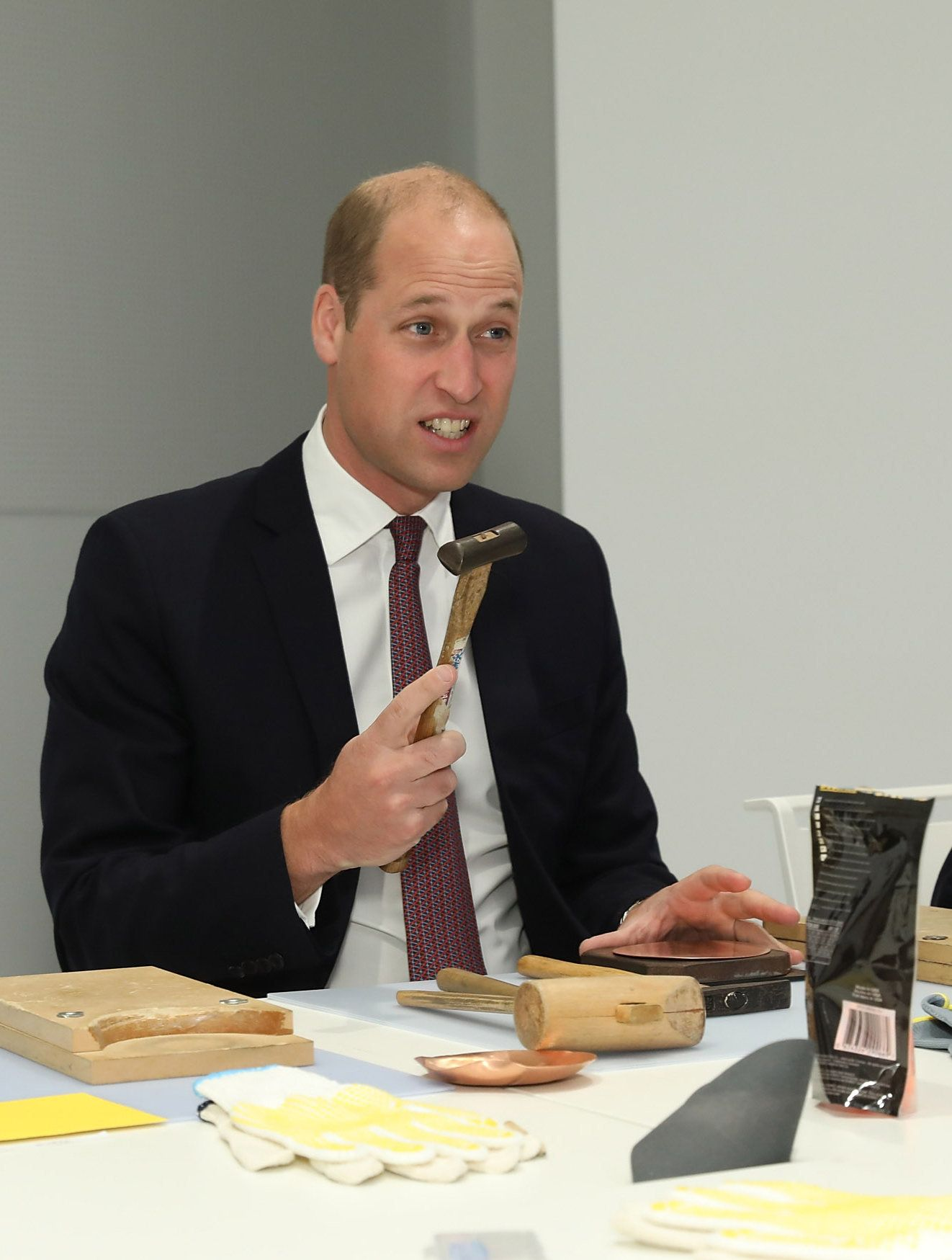 Britain's Prince William, Duke of Cambridge joins local school children at a copper beating workshop during the official opening of Japan House, the new Cultural Home of Japan in London on September 13, 2018. (Photo by Tim P. Whitby / POOL / Getty Images)        (Photo credit should read TIM P. WHITBY/AFP/Getty Images)
