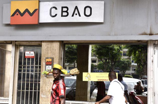 À Dakar, deux hommes passent devant une agence de la CBAO, première banque sénégalaise,...