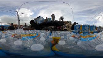 SAN ISIDRO, PUERTO RICO - OCTOBER 17:  (EDITOR'S NOTE: Image was created as an Equirectangular Panorama. Import image into a panoramic player to create an interactive 360 degree view) U.S. Army along with other troops deliver FEMA aid more than three weeks after Hurricane Maria hit the island, on October 17, 2017 in San Isidro, Puerto Rico. The area is without running water or grid power. Puerto Rico experienced widespread damage including most of the electrical, gas and water grid as well as agriculture after Hurricane Maria, a category 4 hurricane, swept through.  (Photo by Mario Tama/Getty Images)
