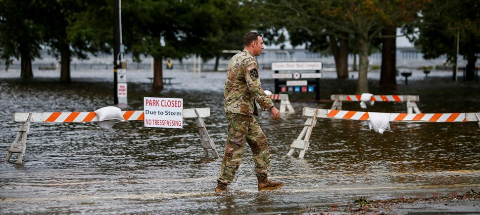 A member of the U.S. Army walks near the flooded Union Point Park Complex as Hurricane Florence comes ashore in New Bern, Nor