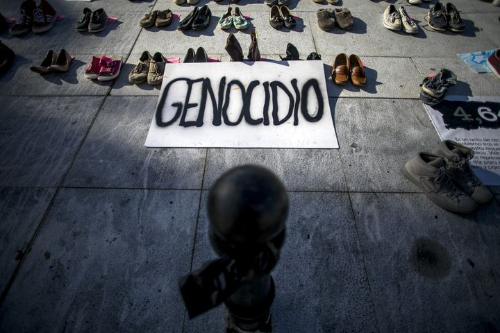"A sign that says ""genocide"" in Spanish is displayed next to empty shoes as part of the June 1, 2018, protest outside the Capi"
