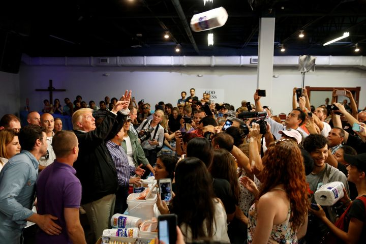 President Donald Trump tosses rolls of paper towels to people at a hurricane relief distribution center in San Juan on Oct. 3
