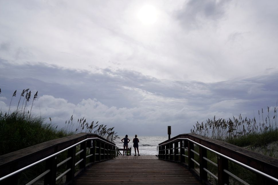 People look out over the surf before Hurricane Florence comes ashore on Carolina Beach, North Carolina, on Sept. 13, 2018.