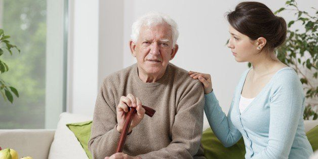 Image of elderly man with walking stick and his carer