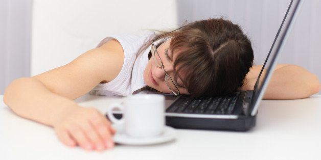 Young woman comically sleeps on laptop at office