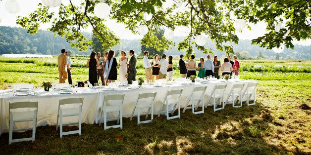 Wedding party having appetizers and drinks beside banquet table in field under tree
