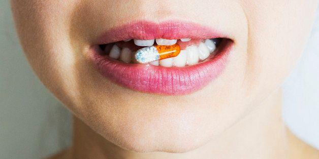 Woman biting multi coloured medical capsule