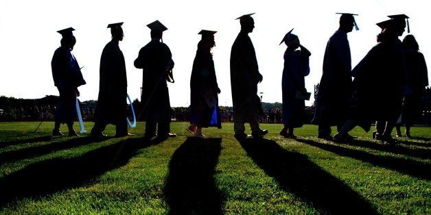 Graduates march onto grassy field during graduation ceremony, sunset and back lighting create silhouette figures.
