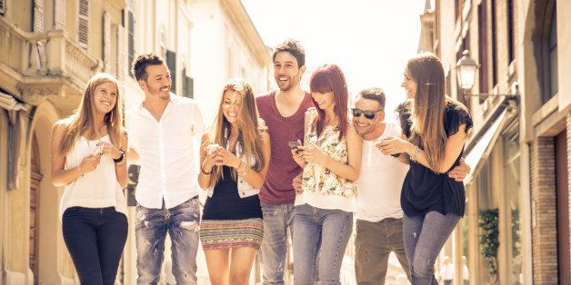 group of friends meeting in the city center. they are having fun with smart phones and walking together