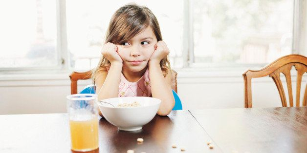 Girl (3-5) sitting at table with cereal, head in hands