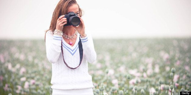 Young photographer in opium poppy field.