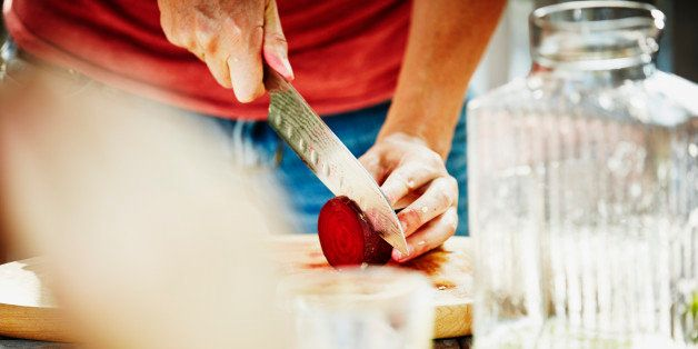 Woman slicing organic beet on cutting board at table on outdoor patio