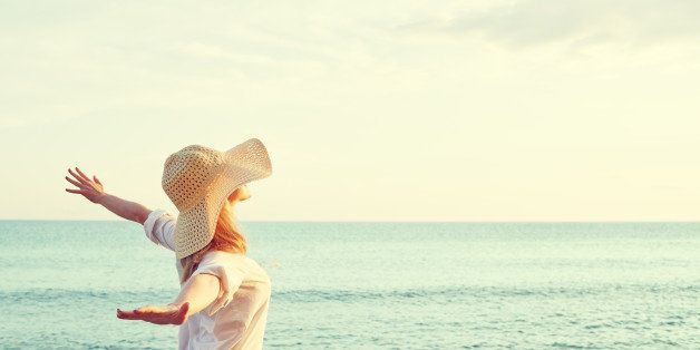 Happy beauty woman in hat is back opened his hands, relaxes and enjoys the sunset over the sea on the beach