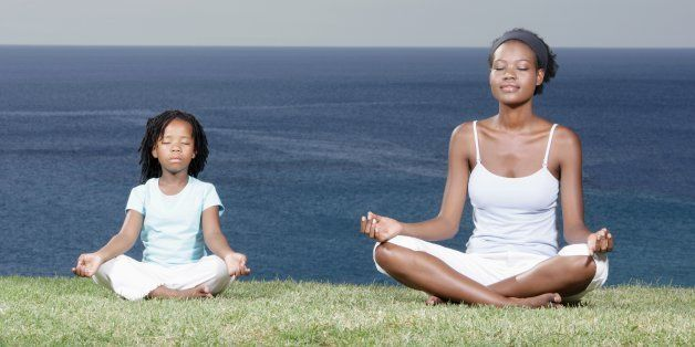 Mother and daughter (5-7) meditating on cliff top, eyes closed