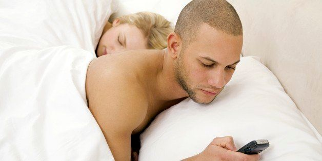 Young man text messaging with young woman sleeping