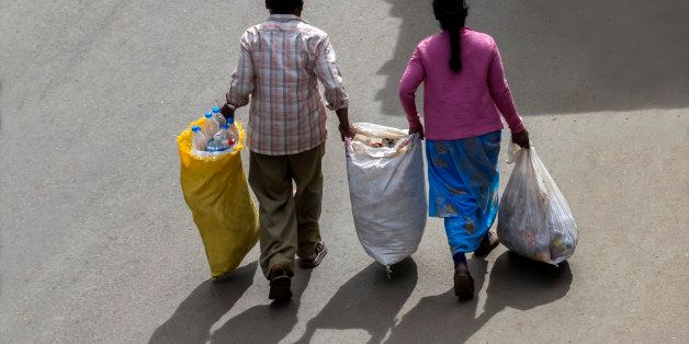 Two road cleaning workers are carrying a large quantity of wastes in bags to disposing dump yard.