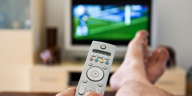 Close up of hand holding a remote control with flatscreen television showing sport in the background. Focus on the OK button.