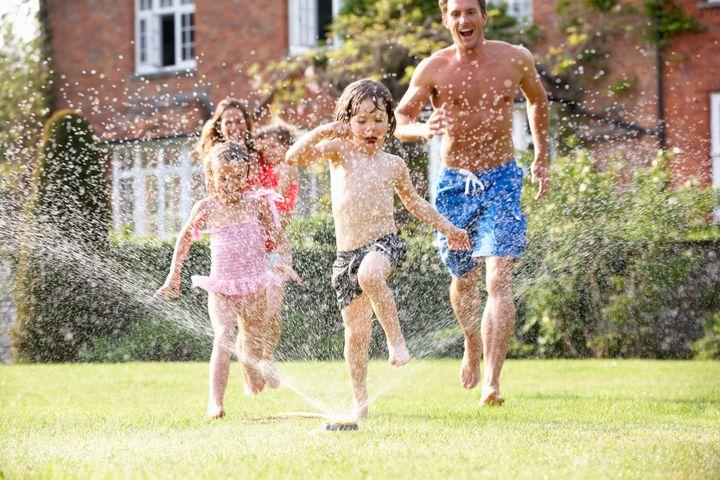 Family Running Through Garden Sprinkler Getting Wet Having Fun