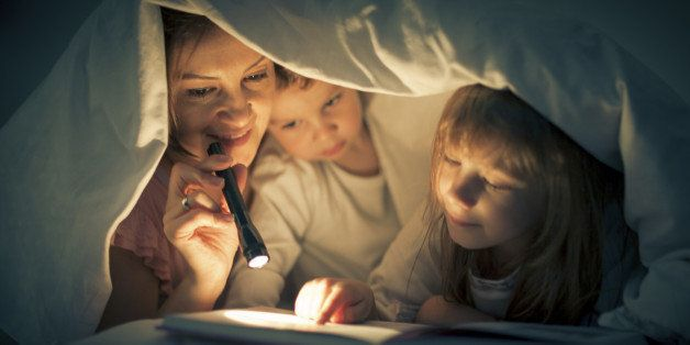 A woman and two children are reading in bed under a sheet.  The woman is holding a small black flashlight.  The little boy is near the mother.  Next to him, the little girl is holding her finger on the page of the book.
