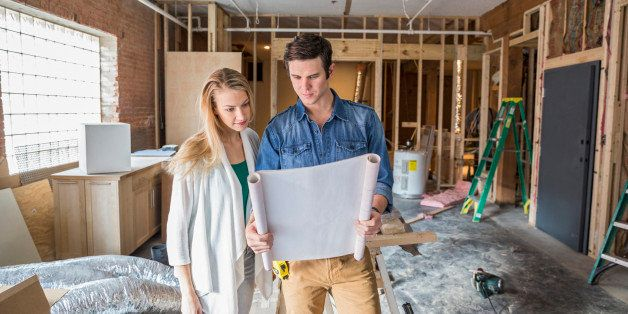 Caucasian couple reading blueprints at construction site