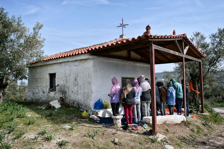 A picture taken on March 16, 2017 shows African Christian migrants praying at a hill church near the Moria migrant camp on th