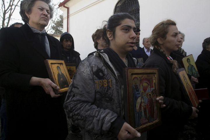 Christian Orthodox Iranian migrants hold icons during a Mass at a church in Idomeni, Greece, March 20, 2016.