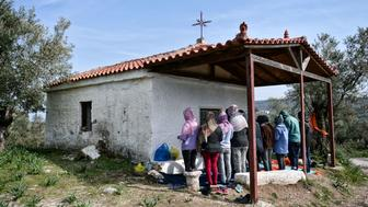 TOPSHOT - A picture taken on March 16, 2017 shows Christian African migrants praying at a hill church near the  Moria migrant camp on the island of Lesbos, almost a year after an EU-Turkey deal.  The deal, signed on March 18, 2016, has sought to stem the flow of migrants from Turkey to the EU, in particular Greece, by land and sea routes.Some 3000 refugees and migrnts live in the Moria camp , out of some 14000 stucked on the Aegean islands since the closing of the borderss and the implementation of the deal. / AFP PHOTO / LOUISA GOULIAMAKI        (Photo credit should read LOUISA GOULIAMAKI/AFP/Getty Images)
