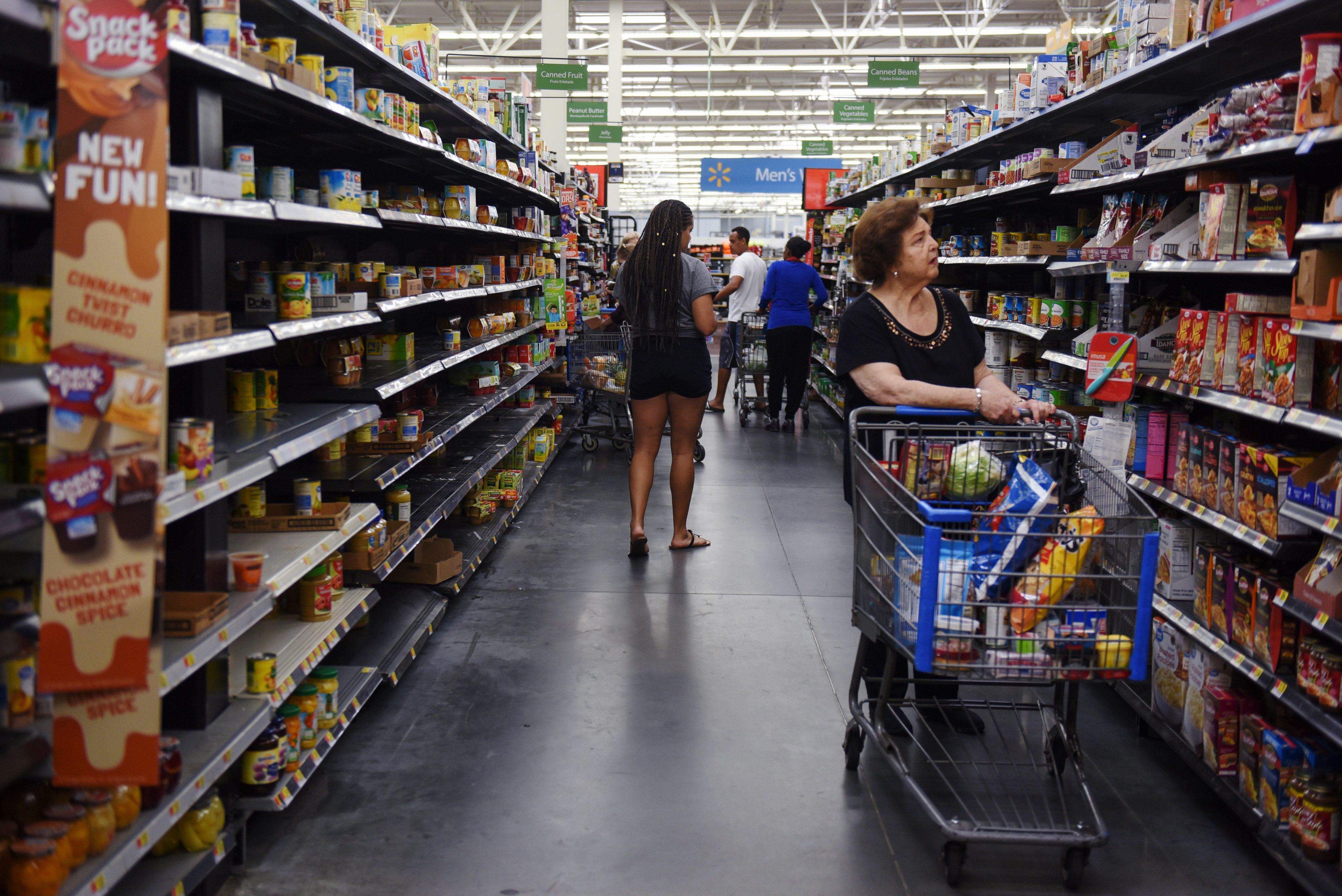 Shoppers walk through a depleted canned food aisle in a Walmart store in Charlotte, North Carolina, as residents prepare Thur