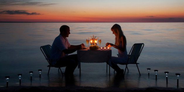 young couple share a romantic dinner with candles on the sea sand beach