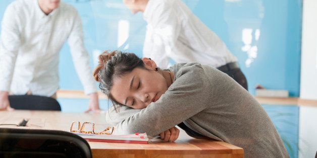 Young businesswoman sleeping during meeting
