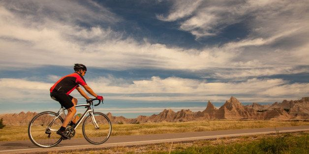 Man cycling on road in the morning in Badlands National Park, South Dakota.