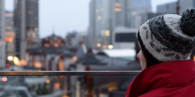 A young woman looking at Tokyo Station at dusk.