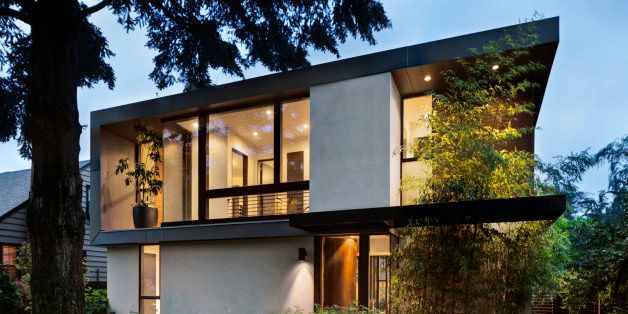 Modern home at twilight with interior and exterior lighting and lush landscaping. Open front door to well lit home interior.