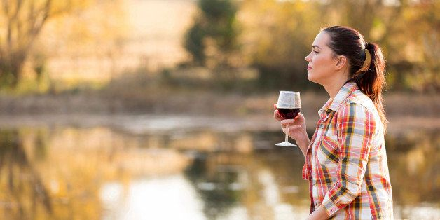 thoughtful young woman with glass of wine on pier in autumn