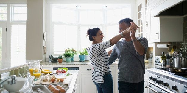 Playful couple dancing in kitchen
