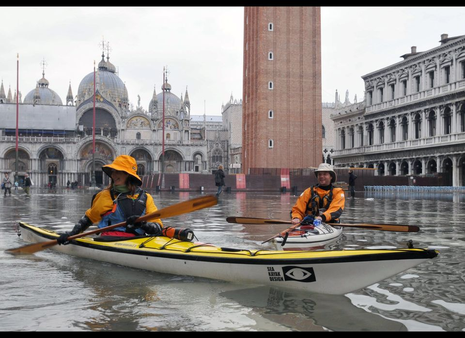 People steer their kayaks on the flooded Piazza San Marco (St Mark's square) during the first 'acqua alta' of the season on N