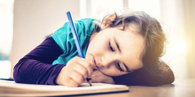 pensive cute little girl drawing at desk with color pen
