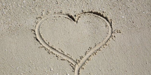 Heart-shape drawn in wet coral and shell sand, Komandoo, Maldives, Indian Ocean.